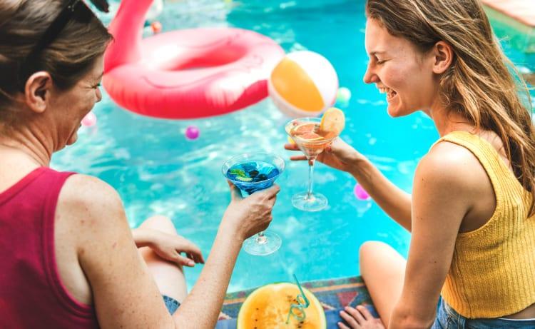Madre e hija brindando frente a un piscina dentro de un hotel en Cali