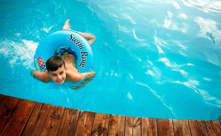 Niño nadando con un flotador en una piscina dentro de un hotel en Cali
